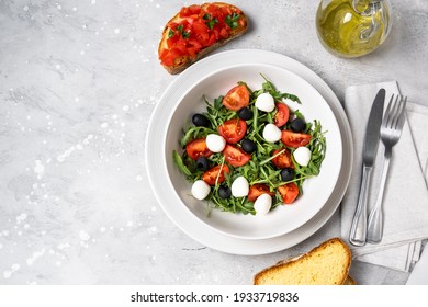 Typical dishes of the Mediterranean diet : mozzarella balls, black olives, olive oil, salad with tomatoes and arugula, bruschetta. Healthy Food Italian cuisine.