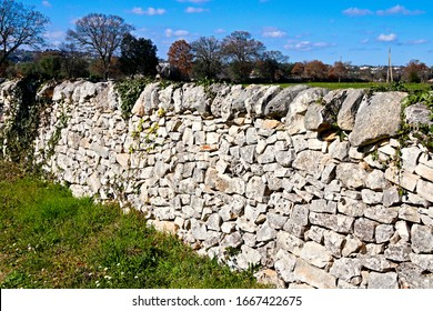 Typical dry stone wall in the countryside of Puglia, southern Italy. These structures are constructed from carefully selected interlocking stones, without any mortar to bind them together