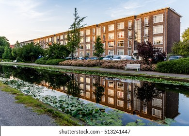 Typical dutch apartments in the city the hague. Reflection in the ditch in front of the building. Photo taken at dusk in a recreational park.