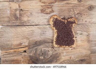 Typical Dutch bread with chocolate hagelslag on wooden background