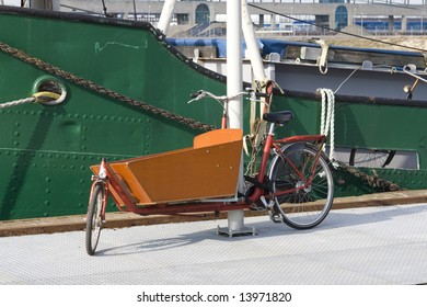 Typical dutch carrier bicycle parked near a house boat. Modern urban parents use these carrier bikes to transport their children.