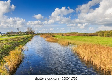 Typical Dutch flat polder landscape with ponds, Reed belt and canals with old and new bridges against blue sky with scattered clouds