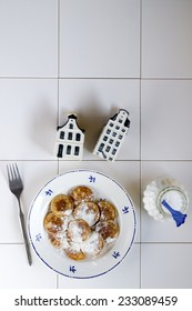 Typical Dutch food called poffertjes  with delfs bleu houses and a sugar pot ,on a white background