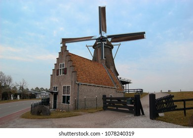 Typical Dutch house and mill at a dike. Medemblik, the Netherlands.