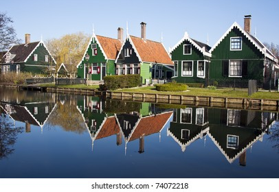 typical dutch houses reflected in water on a sunny spring day