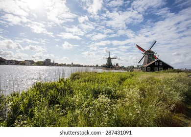 Typical Dutch landscape with windmills along a river in Zaanse Schans, Noord-Holland, The Netherlands