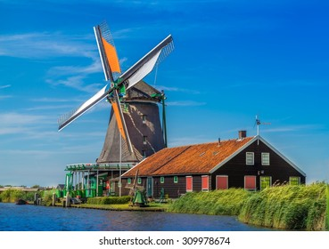 Typical Dutch view of a windmill and farmhouse near a river