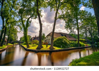 Typical dutch village of Giethoorn in Netherlands with a local canal and high trees. Giethoorn is often referred to as Little Venice, or the Venice of the North. Long exposure.