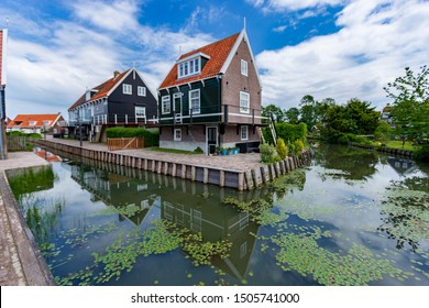 Typical Dutch village scene with wooden houses over canal on the island of Marken in the Netherlands, Holland