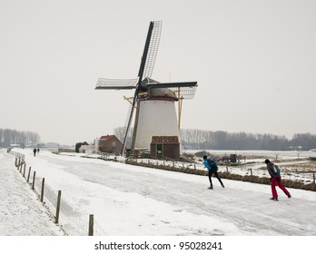 Typical dutch winter: windmill and ice skaters