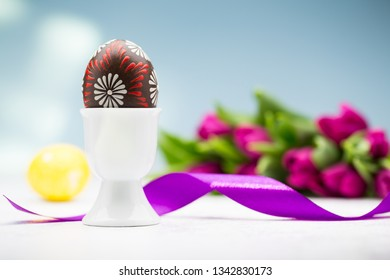 Typical easter egg from Slovakia with egg holder, ribbon and tulips.