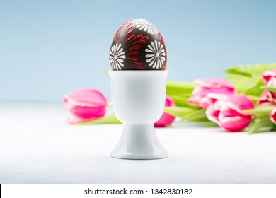 Typical easter egg from Slovakia with egg holder and tulips.