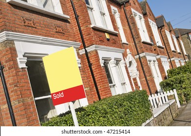 "Typical English home with a ""Sold"" sign."