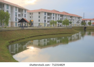 typical facade of a modern town suburban house near the pond at noon with reflection on the lake