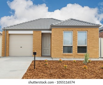 typical  facade of a new small brick modern suburban  house against cloudy sky