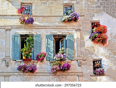 Typical facade of the old Provencal retro house with windows and wooden shutters decorated with colorful fresh flowers in Provence, Cote d'Azur, France