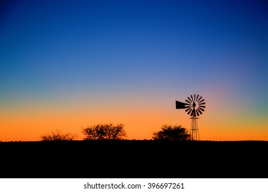 A typical farm setting in the morning with a wind pump and the sun about to rise in the background. Slight movement in the blades of the wind pump from the wind blowing it on.