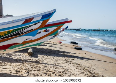 Typical fishing boats in Yoff Dakar, Senegal, called pirogue or piragua or piraga. Colorful boats used by fishermen standing on the beach.
