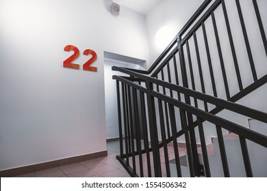 "A typical flight of stairs in an office business skyscraper: clean white walls, metal fencing of the stairway, bright light, door to the floor, big orange digits ""22"", and the fire alarm speaker above"