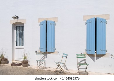 Typical French house with blue blinds and bistro chairs