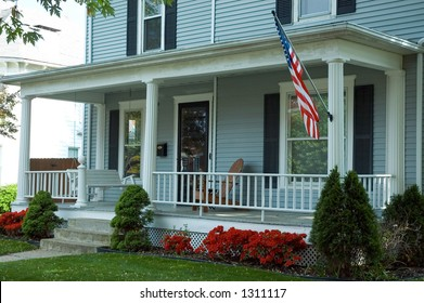 A typical front porch of a home in a small town in  the U.S.A. Featuring an American flag proudly flying and a porch swing to enjoy the spring day.