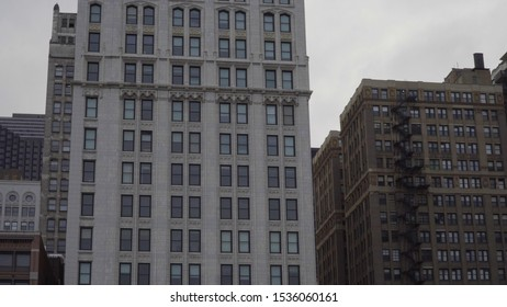 Typical generic day time establishing shot of an urban apartment building facade. Fire escape on outside of facade for safety