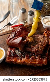 Typical german beer restaurant meals: baked ribs with pickled snacks around