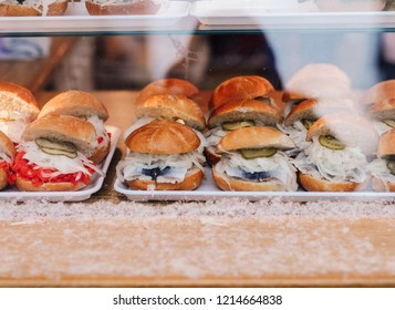 Typical german fish sandwiches made of rolls or buns with Bismarck herring or salmon lox, onions and pickles at Nuremberg Christmas market stall, Bavarian fast food