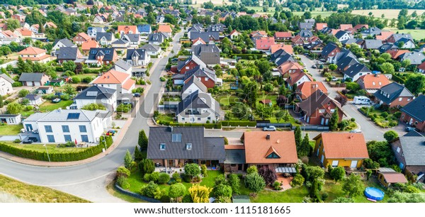 Typical German new housing development in the flat countryside of northern Germany between a forest and fields and meadows, made with drone