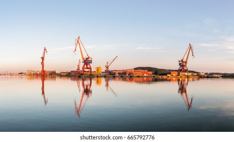 Typical Gothenburg picture with shipyards cranes and water during sunrise.