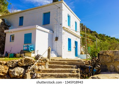 Typical Greek architecture concept. Big white square house with blue window shutters during summer day.