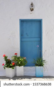 Typical greek blue door on white wall and facade of house, greece