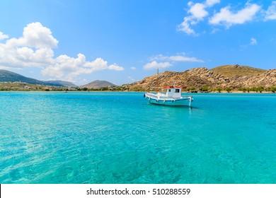Typical Greek fishing boat sailing on turquoise sea water on Paros island, Greece