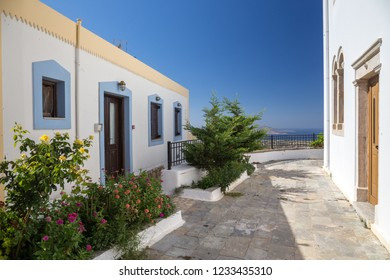 Typical greek street with white buidings and plants