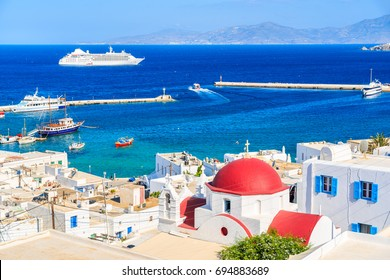 Typical Greek white church with red dome and view of Mykonos port, Mykonos island, Cyclades, Greece