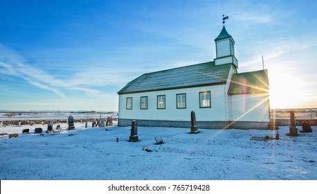 Typical green colored wooden church, Iceland in winter. Sunrise light