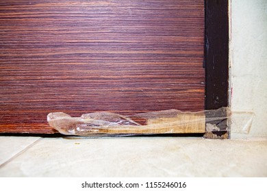 Typical home improvement problem. Miserable, bad and lousy self attempt to temporary fix the problem of chipped and damaged skin of wooden veneer door. Might need professional carpenter repair service