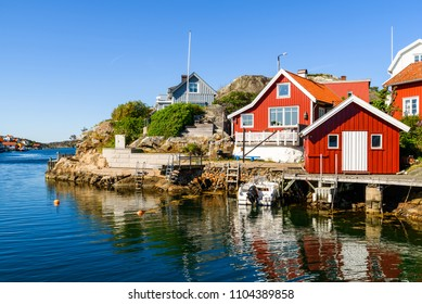 Typical homes and buildings at the seaside village of Kyrkesund on Tjorn, Sweden. It is a sunny and calm day at the coast.