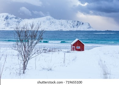 A typical house of the fishermen called rorbu on the snowy beach frames the icy sea at Ramberg Lofoten Islands, Norway, Europe