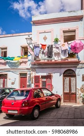 A typical house with a line of washed clothes and a red car parked by the door in Iglesias, Sardinia