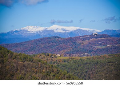 typical house (masia) and small church (ermita) im a climb with Autumn oak and pine forest with a snowed pirineo mountains background