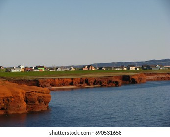 Typical houses on top of red cliffs in Magdalene Islands, iles de la Madeleine, Quebec, Canada