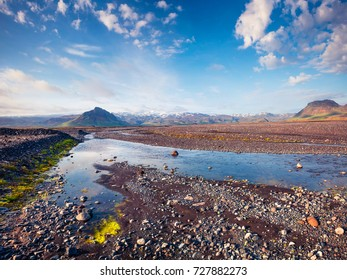 Typical Icelandic landscape with volcanic ground and pure water rivers. Colorful sunny scene in the south Iceland, Europe. Beauty of nature concept background.