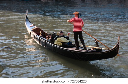A typical and iconic image of Venice, Italy, a Gondolier leads his gondola with two tourists on a beautiful sunny day