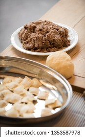 Typical Italian agnolotti, dough and a white plate full of stew meat sauce on a wooden board