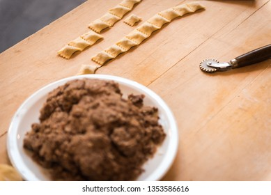 Typical Italian agnolotti, a pasta cutting wheel and  a white plate full of stew meat sauce on a wooden board