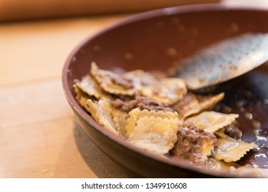 Typical Italian agnolotti with stew ragù in a brown soup plate on a wooden cutting board