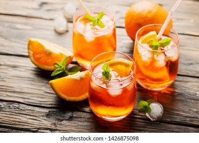 Typical Italian aperitif Aperol Spritz with orange, ice and mint, selective focus image