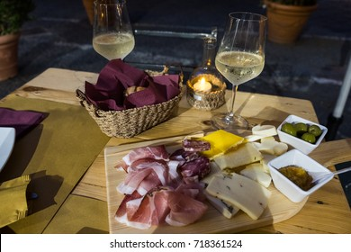 A typical italian aperitif with stem glasses of frozen white wine, cured meats and cheeses