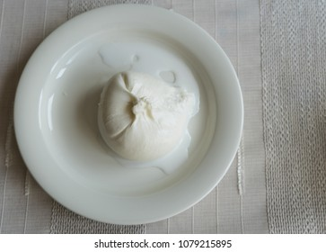 Typical Italian burrata cheese on a white plate on a white tablecloth